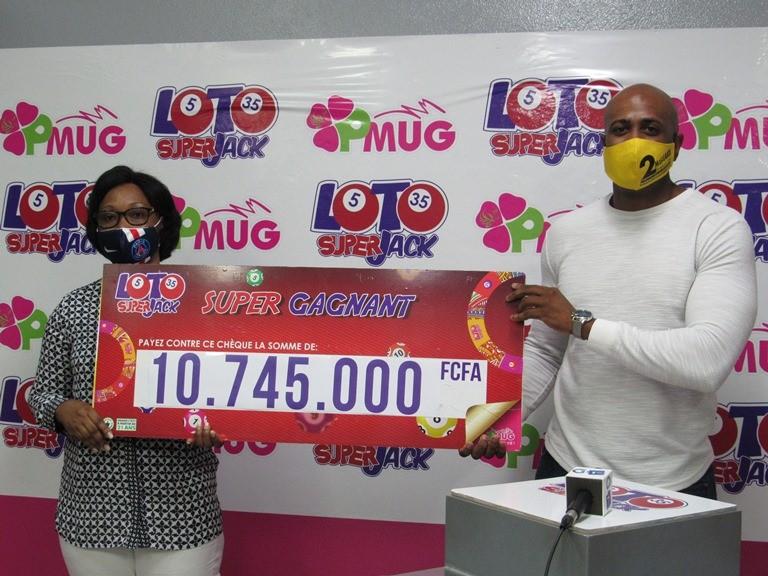 L'heureuse gagnante du Loto Superjack recevant symboliquement son chèque des mains du Directeur commercial du PMUG Lionel Micheau le 29 septembre à Libreville © Gabonactu.com